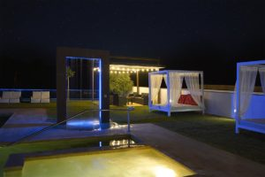 Jardin de noche con camas balinesas